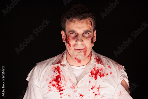 Man dressed up like a zombie for halloween over black background. Wallpaper Mural