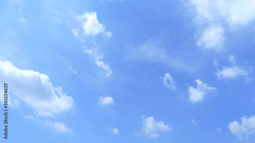 Fototapeta Bright blue sky with small  irregular clouds during the daytime