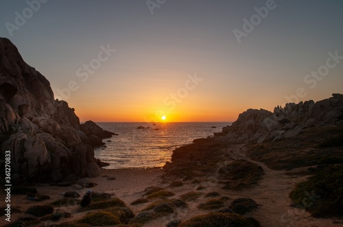 Fototapeta Breathtaking view of cliffs near the calm blue sea at sunset obraz