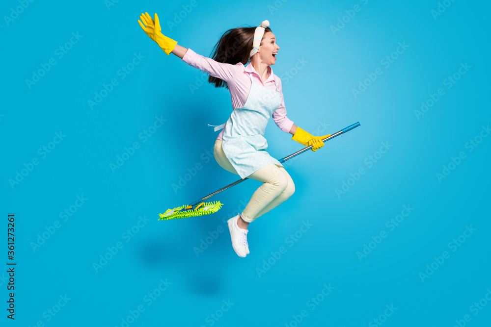 Fototapeta Full length body size profile side view of her she nice attractive funky childish comic maid jumping riding broom like horse isolated on bright vivid shine vibrant blue color background