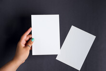 Woman's Hands Are Holding Empty Mock-up Brochure For Writing Letter Above Black Background