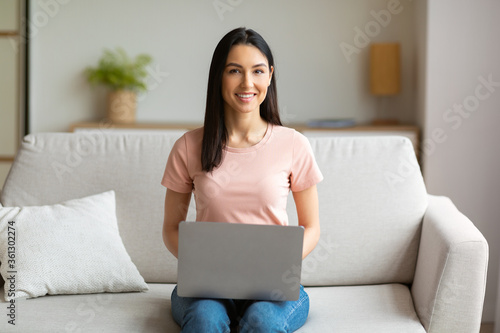 Fotografija Happy Woman With Laptop Computer Sitting On Sofa Working Indoors