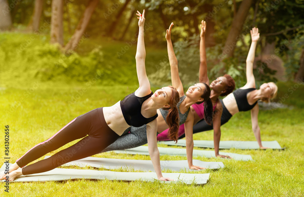 Fototapeta Diverse young women practicing yoga together at park on summer day