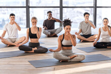 Young Men And Women In Yoga Studio Practicing Alternate Nostril Breathing Exercises