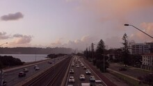 Overhead Time Lapse Shot Of Busy Freeway As Sun Sets. Trains Pass Up Middle Of Lanes, Car Headlights Begin To Glow.  Storm Clouds Fly Overhead And Light Rain Drifts Past. Swan River Abuts Highway