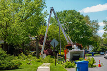 Large Bucket Crane Truck With A Long Arm Is Seen In Front Of A House Where A Large Tree Is Partially Cut Down
