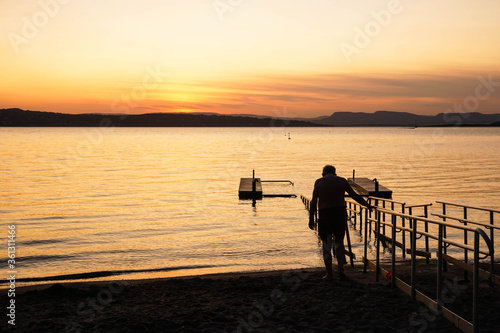 Old man walking across a bridge into the water on a sunset Canvas Print