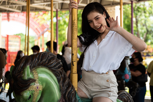 Fotografering Young woman enjoying ride go around in the amusement park.