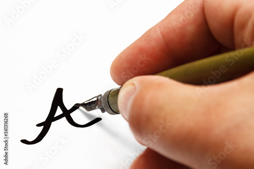 Fotografia, Obraz a man's  hand holds a old dip pen