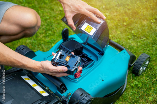 Obraz man putting battery into electric cordless lawn mower - fototapety do salonu