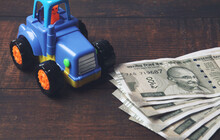 Plastic Toy Tractor With Indian Currency On Wooden Table - Vehicle Loan Concept