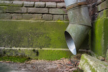 A Pipe For Draining Rainwater On The Wall Of A House With Green Mold Around