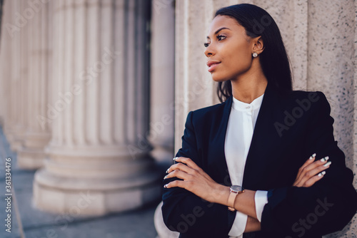 Fotomural Female African American banker dressed in elegant black suit folding hands and looking on side standing against office building