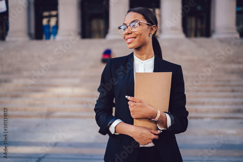 Successful African American graduate juridical specialist standing outdoors against courthouse building with folder in hands Fotobehang