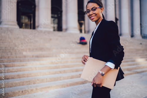 Photo Half length portrait of positive woman executive dressed in elegant suit standing in city outdoors