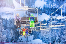 Boy And Girl Sit On Chairlift With Friends Going On Second Chair All Kids In Colorful Outfit Over Snow Forest On Background
