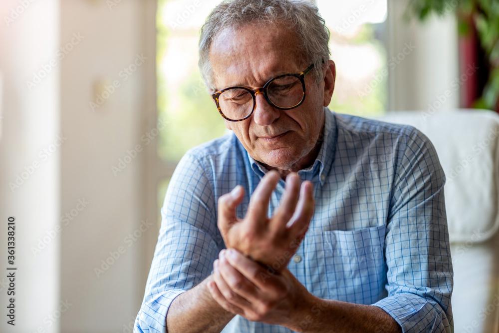 Fototapeta Senior man with arthritis rubbing hands