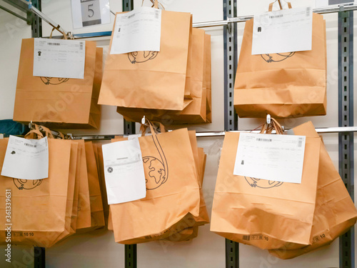 Obraz na plátně Brown paper bags with goods ordered online previously, hanging on the wall