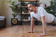 Concentrated middle adult man doing push ups exercise at home