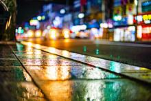 A Photo Of A Sidewalk Reflecting A Headlight.