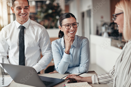 Obraz Three smiling coworkers talking together in an office - fototapety do salonu