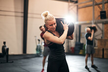 Fit Young Woman Using A Weight Bag At The Gym