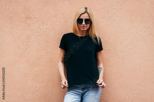 Obraz na plátne Stylish blonde girl wearing black t-shirt and glasses posing against street , urban clothing style