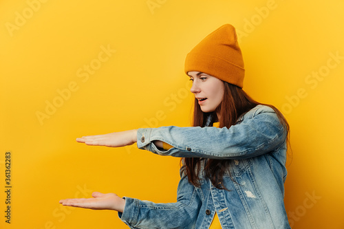 Fototapeta Surprised young woman showing big size gesture with hands, attractive amazed fem
