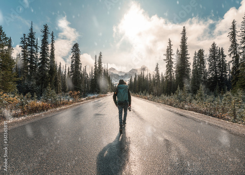 Fotografering Man backpacker walking with snowing in Banff national park