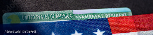 Valokuvatapetti Fragment of Permanent resident green card covered by flag of USA