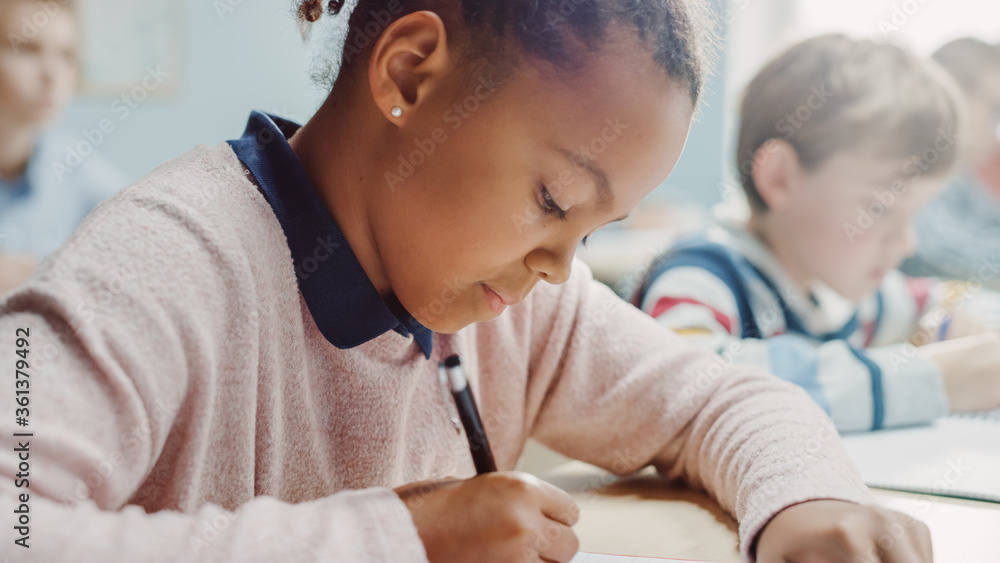 Fototapeta In Elementary School Classroom Girl Writes in Exercise Notebook, Taking Test. Junior Classroom with Diverse Group of Bright Children Working Diligently, Learning. Side View Portrait