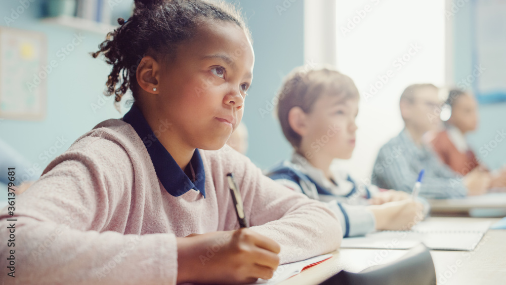 Fototapeta In Elementary School Classroom Black Girl Writes in Exercise Notebook, Taking Test. Junior Classroom with Diverse Group of Bright Children Working Diligently, Learning. Low Angle Side View Portrait