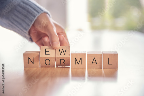 Fotomural Woman hand arranging wooden cubes with NEW NORMAL word