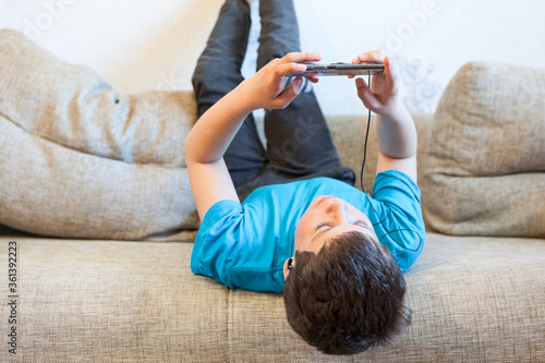 Photo Lazy preteen boy playing game with his cellphone, child lying back on couch in d