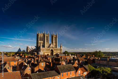 Fotografie, Obraz West Front of Lincoln Cathedral over rooftops with lots of sky room, Lincoln, Li