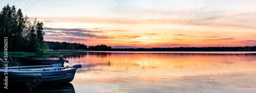 Fototapeta Scandinavian white night in Sweden. View at midnight Sun just below horizon line, golden sun rays illuminate highest clouds in atmosphere. Lake and forest at coast line. Blurry close view at boats obraz