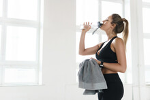 Tired Sweaty Woman Drinks Water After Fitness Workout In The Gym