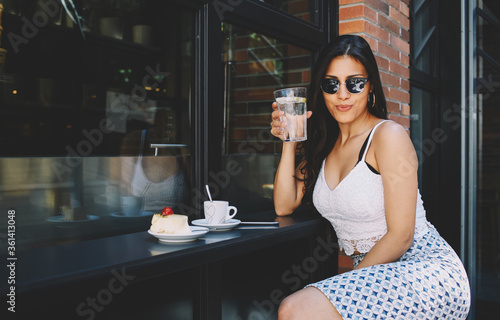 Fotografie, Obraz Modern arabic woman with excellent ideal figure dressed in stylish clothes sits