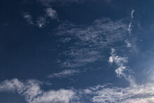 Small Tufts Of White Cloud, Floating Together Under A Dark Blue Sky.