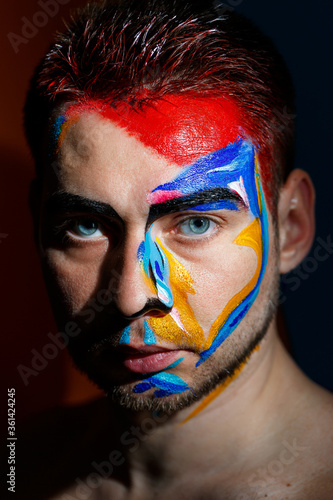 Portrait of a young man with colored paint on a dark background. Professional Makeup Fantasy Art Makeup