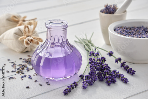 Photo Dry lavender flowers, bottle of essential oil or flavored water, sachet and mortar on white wooden table