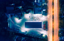 Gas Station, Petrol Station Or Service Station. And Convenience Store, Shop, Grocery, Market, Mart Or Mini Mart. Light From Car On Street, Road. For Shopping, Refueling An Energy. Aerial View At Night