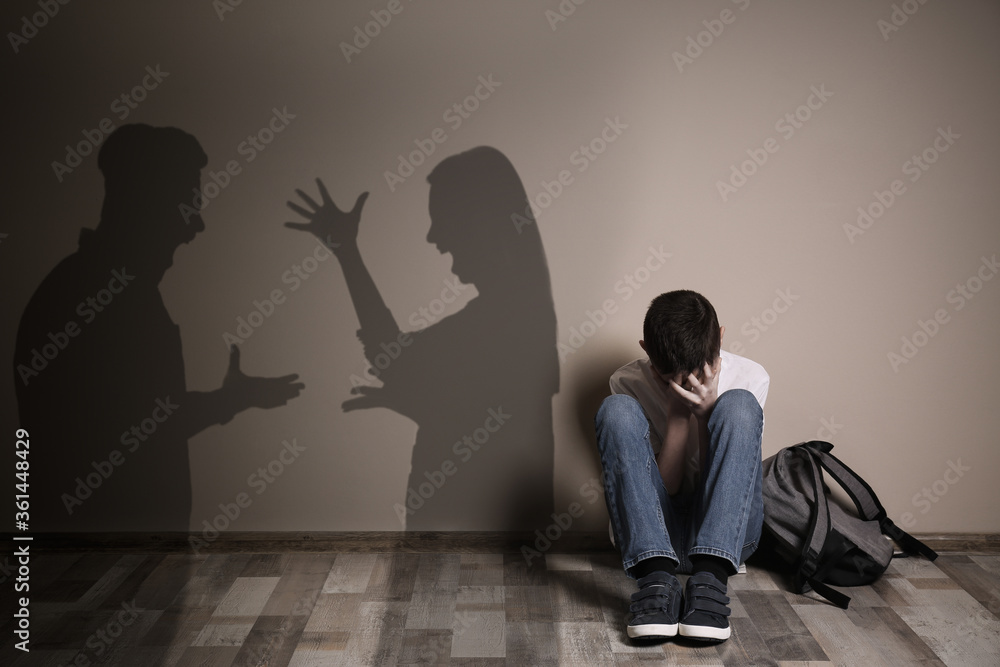 Fototapeta Upset boy with backpack sitting on floor and silhouettes of arguing parents