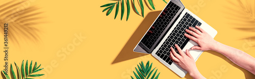 Obraz Person using a laptop computer with tropical leaves from above - fototapety do salonu