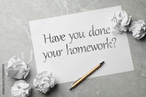 Paper sheet with phrase HAVE YOU DONE YOUR HOMEWORK? on grey marble table, flat Fotobehang