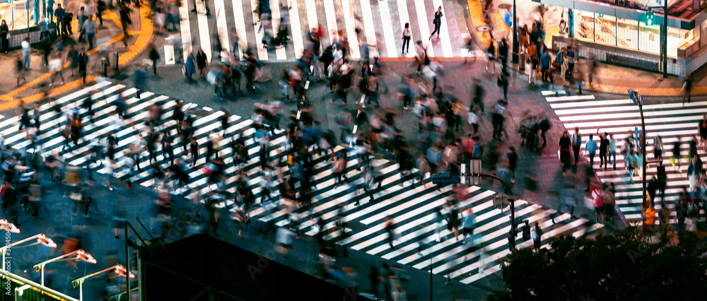 Fototapeta People and traffic cross the famous scramble intersection in Shibuya, Tokyo, Japan, one of the busiest crosswalks in the world