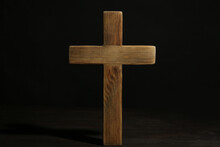 Christian Cross On Wooden Table Against Black Background. Religion Concept
