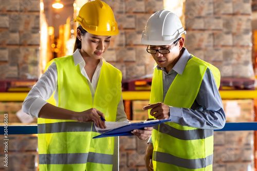 Asian warehouse manager discuss with worker Canvas Print