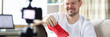 Guy front camera in apartment shows new sneakers. Video blogger demonstrates appearance product. Guy works remotely by shooting video blog and offering goods online. Quality product description
