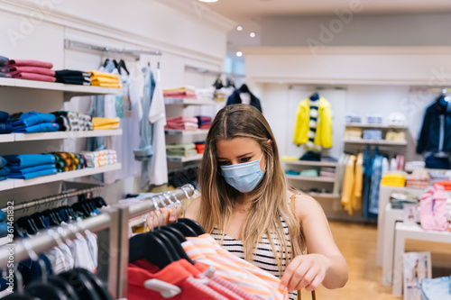 Fényképezés Young Woman in mask shopping at a clothing store in the coronavirus pandemic